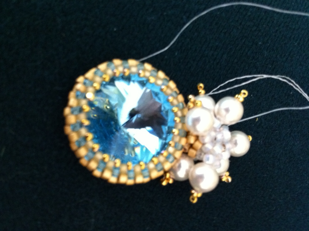 Dark background. An aquamarine rivoli bezeled with gold and aquamarine seed beads, topped with white pearl accents and visible working threads.