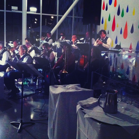 Nighttime in the pavilion at the Olympic Sculpture park. A white wall to the back is covered in colorful raindrops, and in front are the members of the Portage Bay Big Band. They wear white shirts and dark vests and hold various musical instruments.
