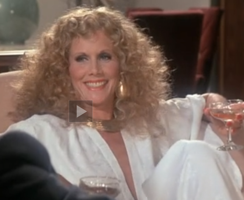 A curly-haired blond woman with pale skin and a sly smile, dressed in flowing white, with bright gold jewelry. She is lounging back on a sofa and looking expectantly to the left.