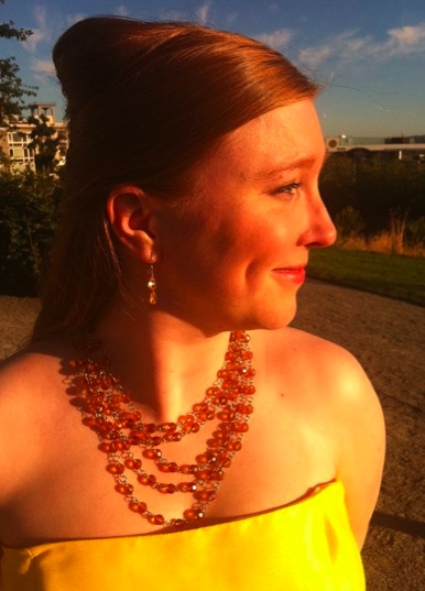 Background is an outdoor patio. Olivia, normally pale of skin, glows golden in the setting sun. Her hair is red, her gown is bright yellow, and her earrings and necklace are glittering amber.