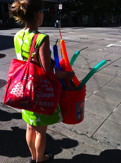 An intersection in the city. A brunette woman with slightly dark skin faces away, wearing a lime-green print sheath dress. She has a large red tote over her right shoulder, and is carrying an orange bucket full of long, thin balloons for the making of animals.