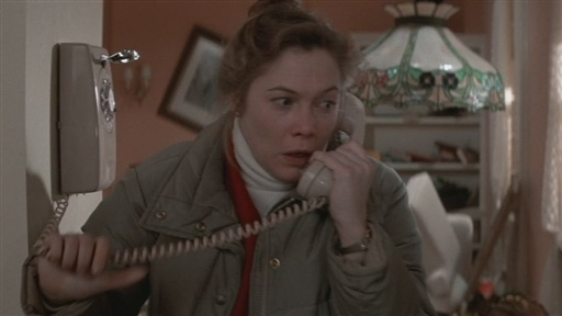 Kathleen Turner as Joan Wilder stands in her New York apartment kitchen, wearing layered shirts and a bulky lavender jacket, hair pulled up in a dowdy bun, holding a phone to her left ear. Her expression is highly concerned.