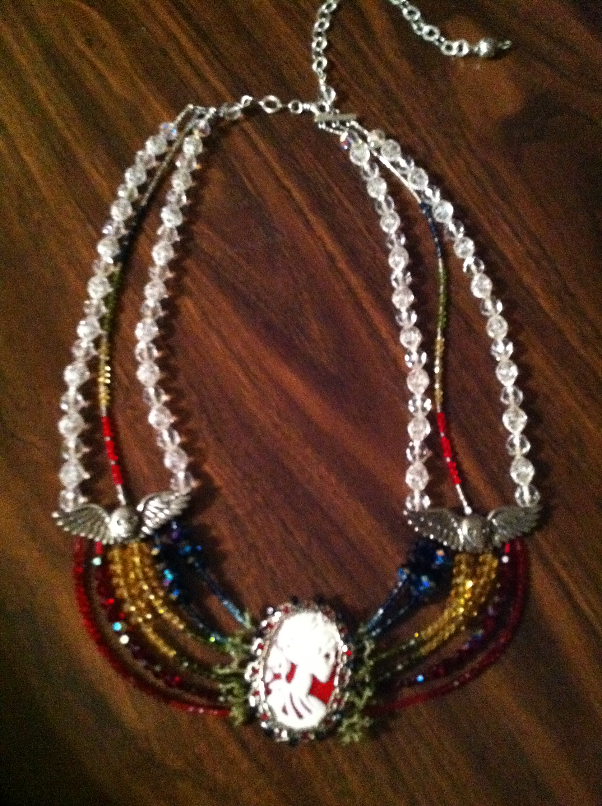 Wood-grain background, on which sits a multi-strand necklace of red, yellow, blue, white, and green crystal, with silver winged skulls and a skeleton lady cameo as centerpiece.
