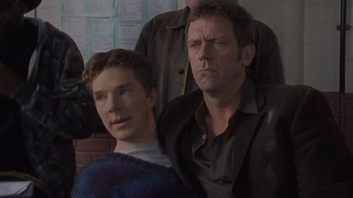 A screencap from I don't know what, with a short-haired Benedict Cumberbatch in a grey shirt and bright blue v-neck sweater, looking left off-frame with his mouth open in preparation for speaking. He is apparently sitting in the lap of Hugh Laurie, clad in black shirt and black jacket, with a bit of a puzzled scowl on his face.