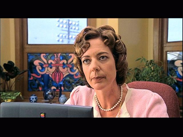 Allison Janney as Ms. Perky: a pale-skinned woman with short, dark, retro-curly hair. She wears a pink suit jacket and a strand of pearls, and is looking very skeptically over the top of her computer monitor.