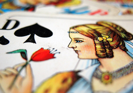 A slanted, narrowly-focused image of the Queen of Clubs from a German deck: a drawing of a pale-skinned woman with blond hair, in a an old-fashioned high-necked gown, holding a bright red flower in her right hand.