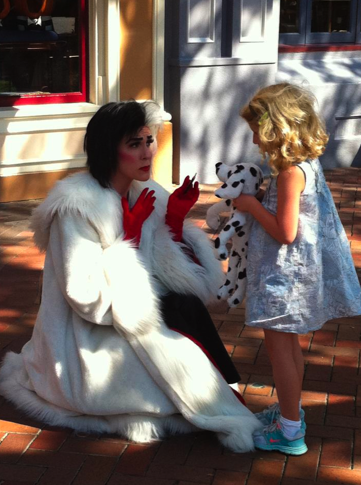 Picture of a golden-haired, pale-skinned moppet with a dalmation puppy toy. The girl is unwisely offering the puppy to a white-fur-coat-clad, red-gloved, black-and-white-haired woman with pale skin, who more often goes by the name of Cruella de Ville.