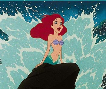 Screencap from The Little Mermaid: Ariel, a pale-skinned mermaid with red hair and a purple seashell bra, poses triumphantly on a spar of rock, while waves burst climactically behind her.