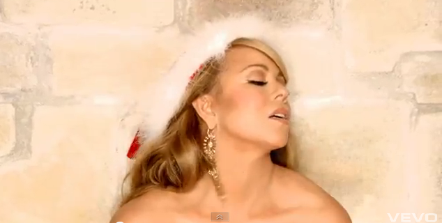 A screencap of Mariah Carey, wearing a Santa hat and large snowflake earrings. Her head is tilted up and to her left, her eyes are closed, and her lips are parted. She leans slightly forward, and the frame cuts off her shoulders and collarbone before her bodice starts so that she appears to be naked.