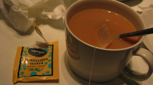 A pale table holds a white teacup, and the teacup holds black tea gone beige with cream and sugar. To the left is an opened yellow packet that once held an Uskollinen Ystävä teabag.