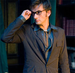 David Tennant in Doctor Who: a tall, lanky, and handsome brunet man with pale skin and a dapper brown suit stands facing the viewer with his head turned to his right. One hand is raised to his face, in preparation for removing his sexy dark-framed spectacles.