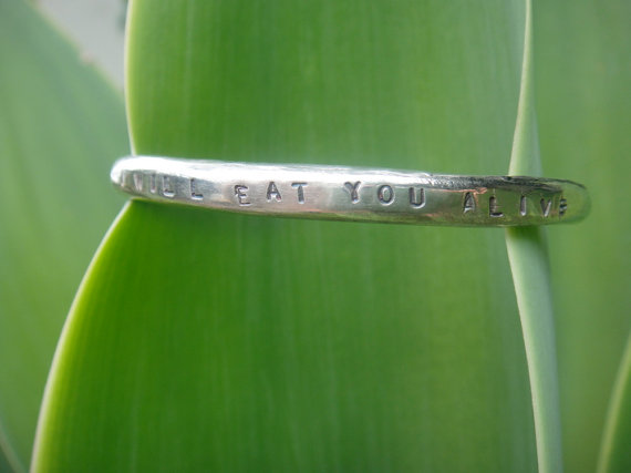 Green leaf holding a silver bracelet, stamped with the words 'I WILL EAT YOU ALIVE,' for which proceeds are (rather inappropriately) offered to juvenile diabetes.