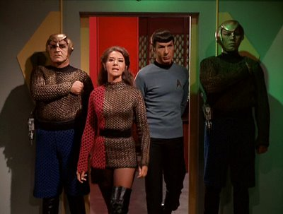 A still shot from 'The Enterprise Incident,' featuring (among other figures) the Unnamed Female Romulan Commander in a long-sleeved, two-tone asymettrical mini-dress with black over-the-knee boots and sheer black hose.