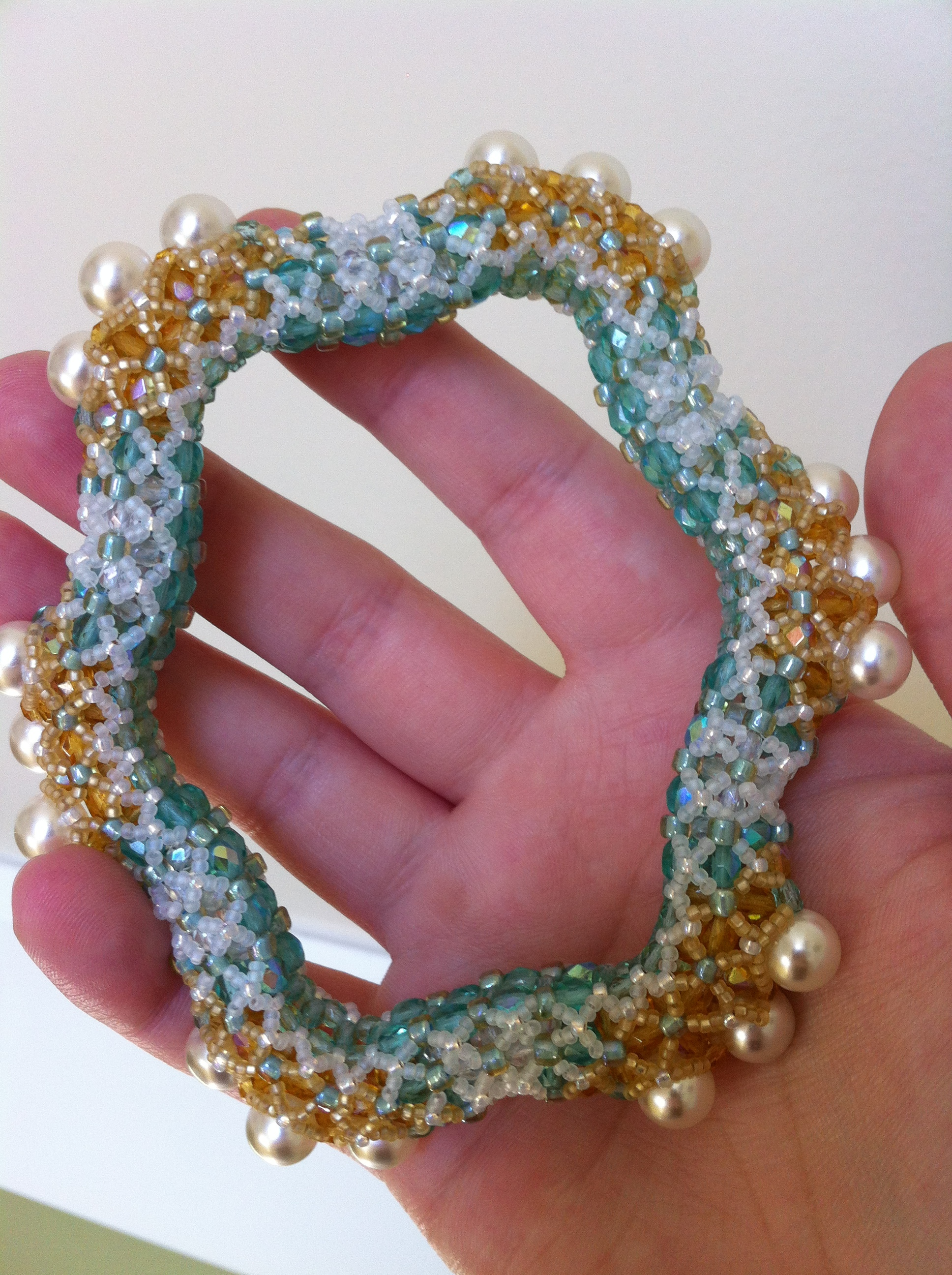 A turquose, white, and gold bangle with pearl accents made of glass, crystal and seed beads. It rests in the palm of a pinkish hand.