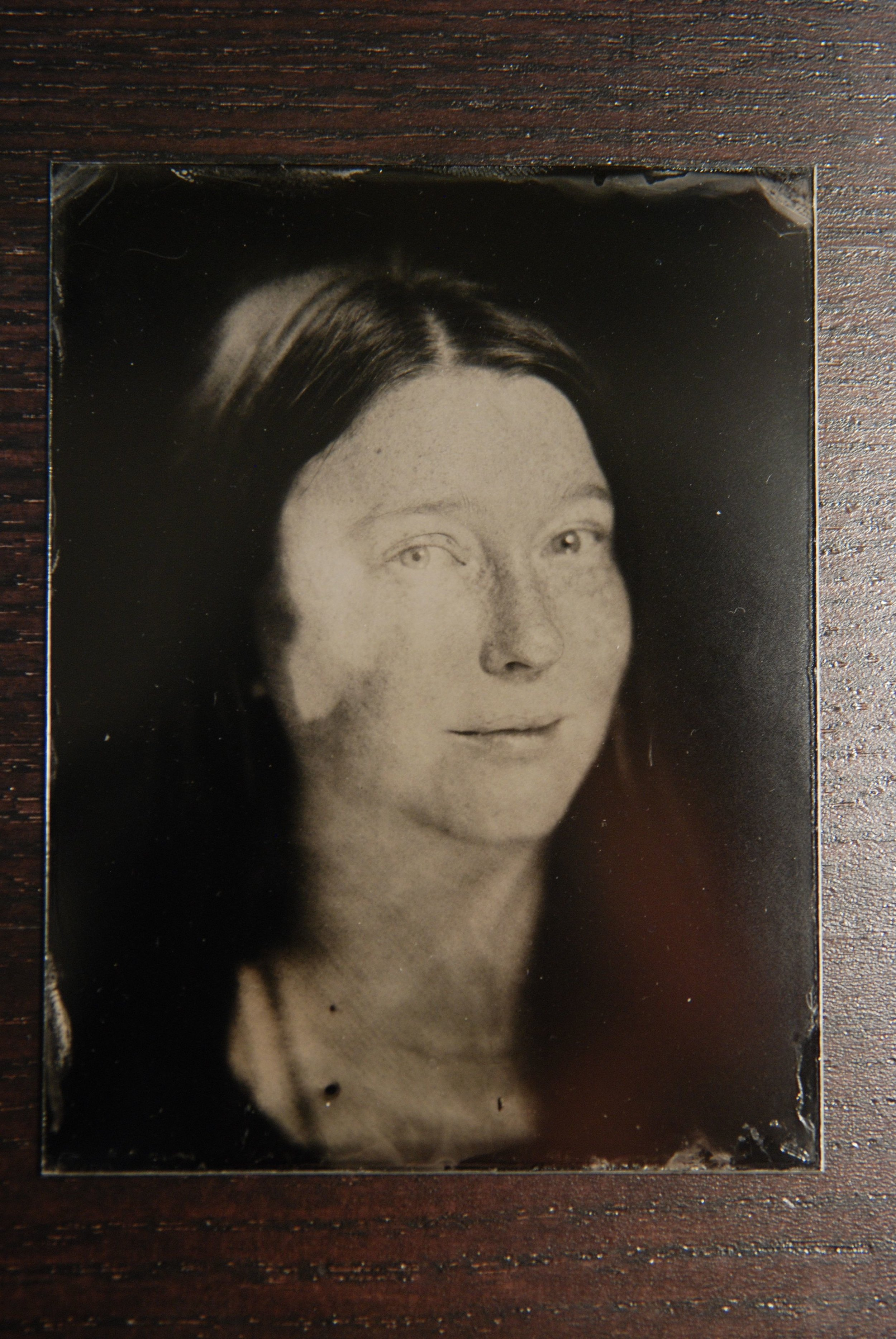 96847c755 Tintype photograph of a dark-haired, fair-skinned woman. She has her