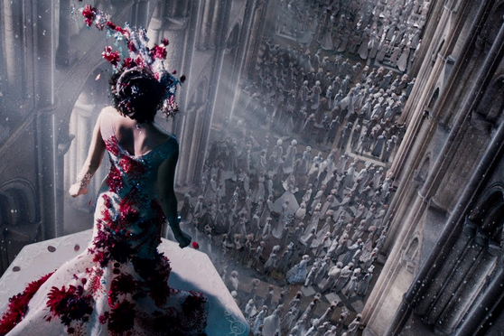 Screen shot from Jupiter Ascending. Jupiter Jones is seen from behind, in a fancy white dress spotted with red feathers and a headdress to match. She faces away from the camera, shoulders tall, while far below her crowds of tiny people look up in awe.
