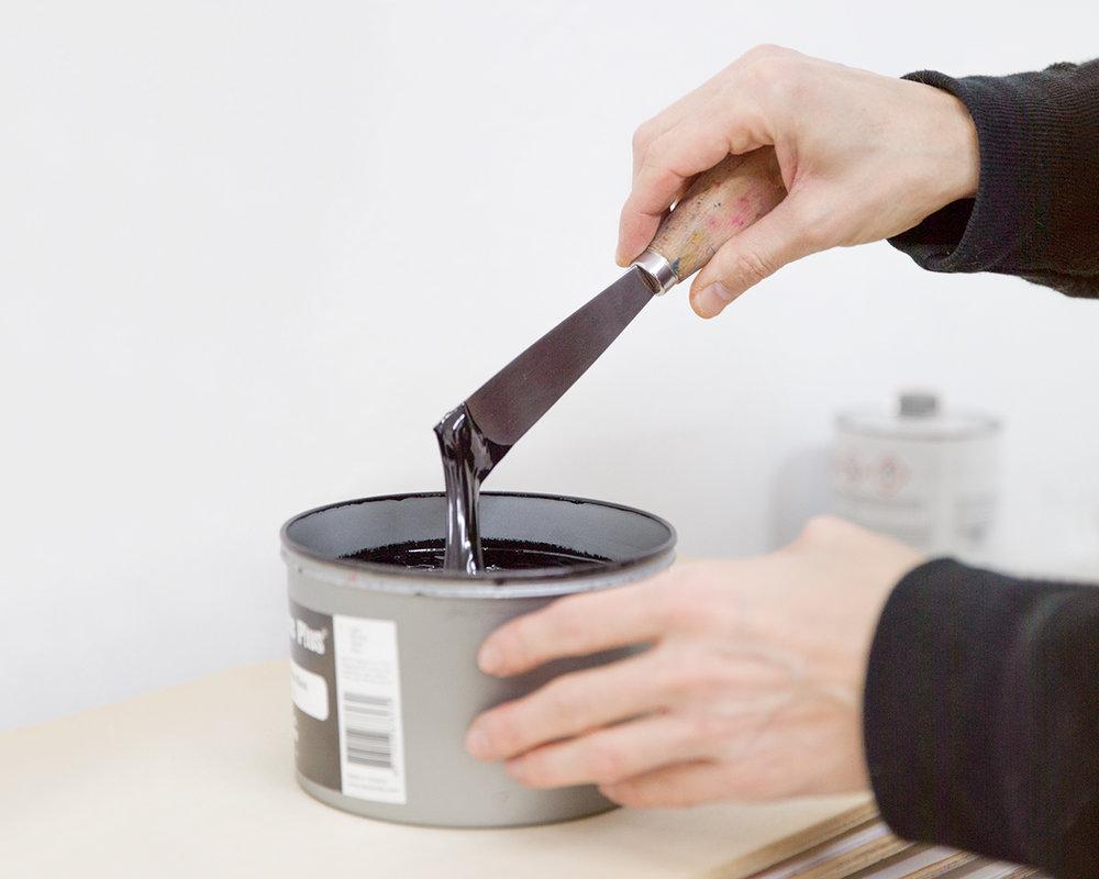 Mit einem Spachtel wird schwarze Farbe aus dem Farbtopf entnommen.