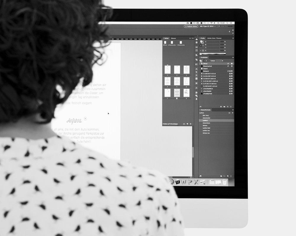 Eine Frau sitzt am Computer und erarbeitet ein Layout.