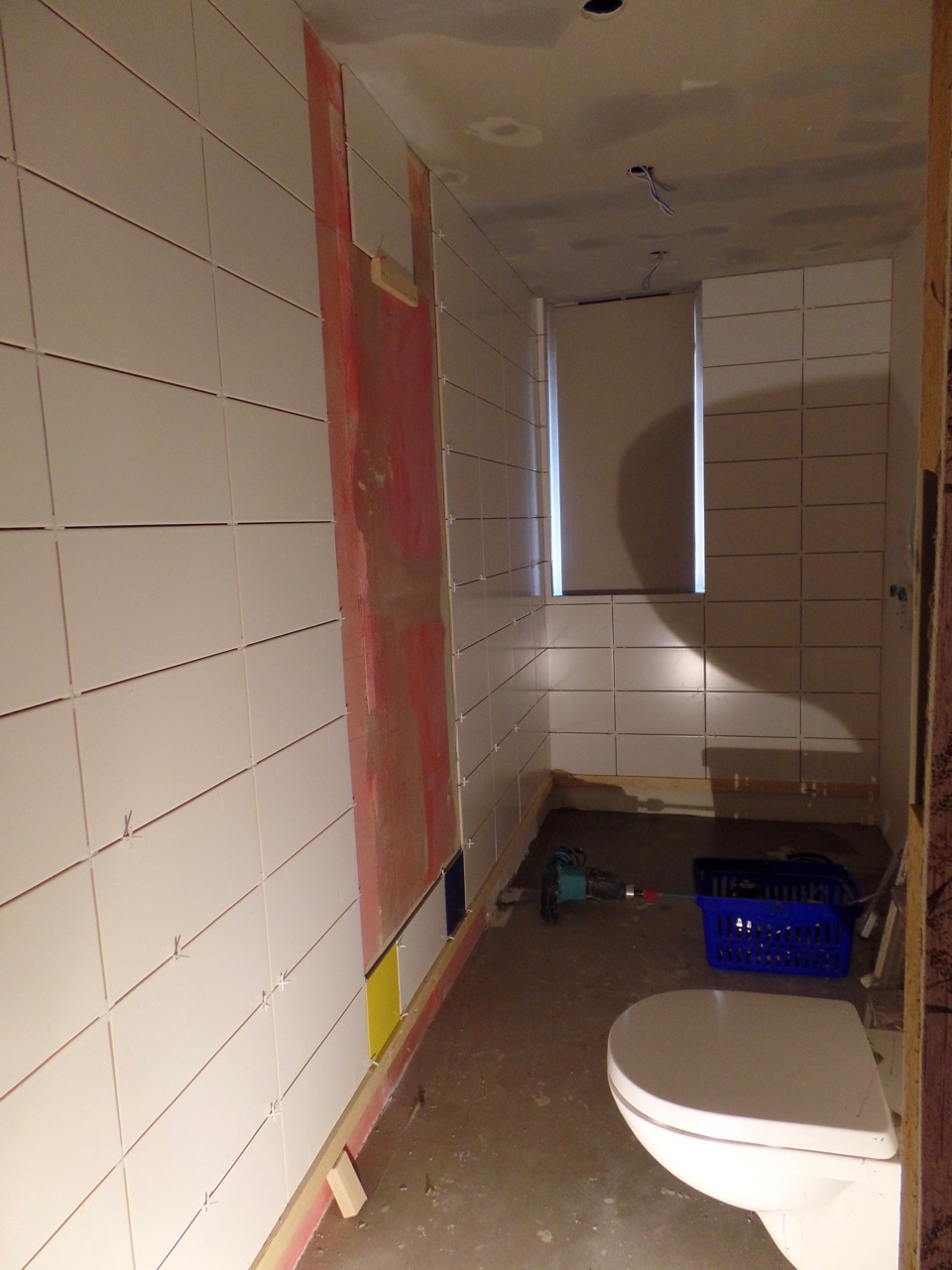 Walls tiled; mirror framing being placed