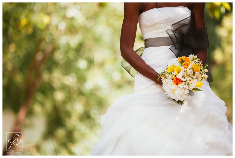 Bride with bouquet and bridal gown with black sash in Woods Park