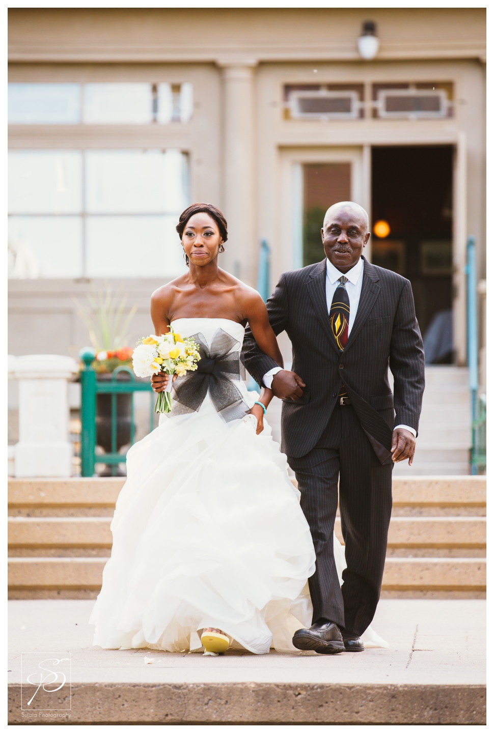 Bride and her father coming down the aisle at her garden wedding at Lougheed House