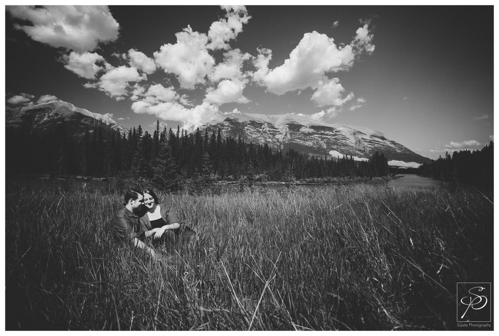 Couple sitting in a field in Canmore, Alberta