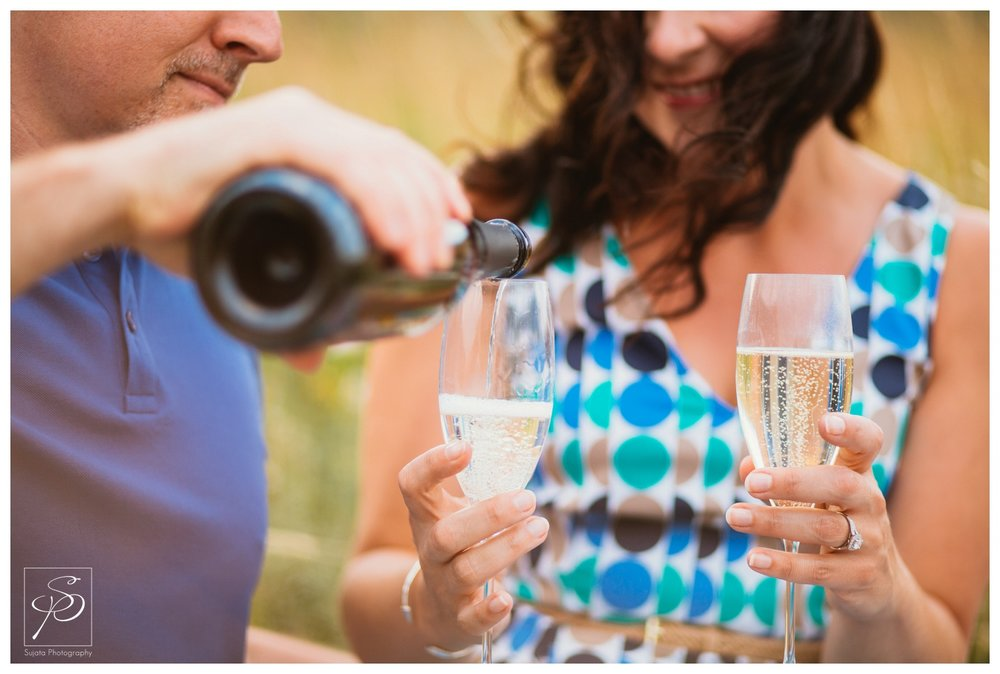 Couple sharing a bottle of champagne during their engagement session