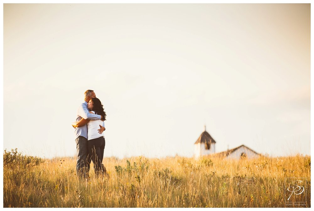 Couple embracing on a field by a Chapel in Ghost Lake, Alberta