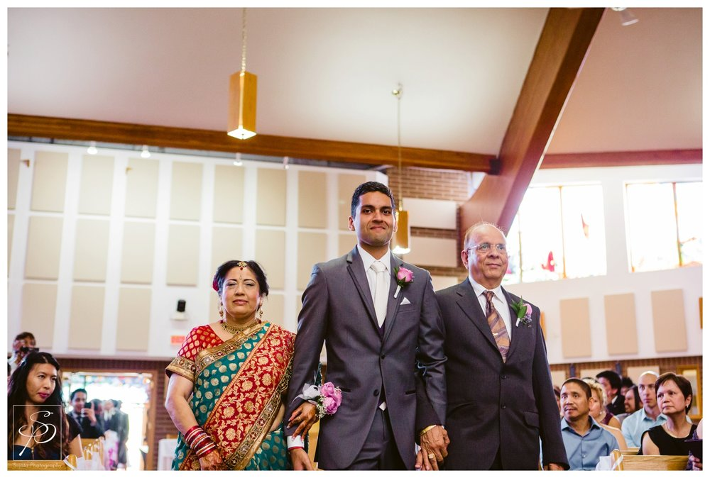 Bride walking down the aisle with his parents at St. Thomas More Calgary