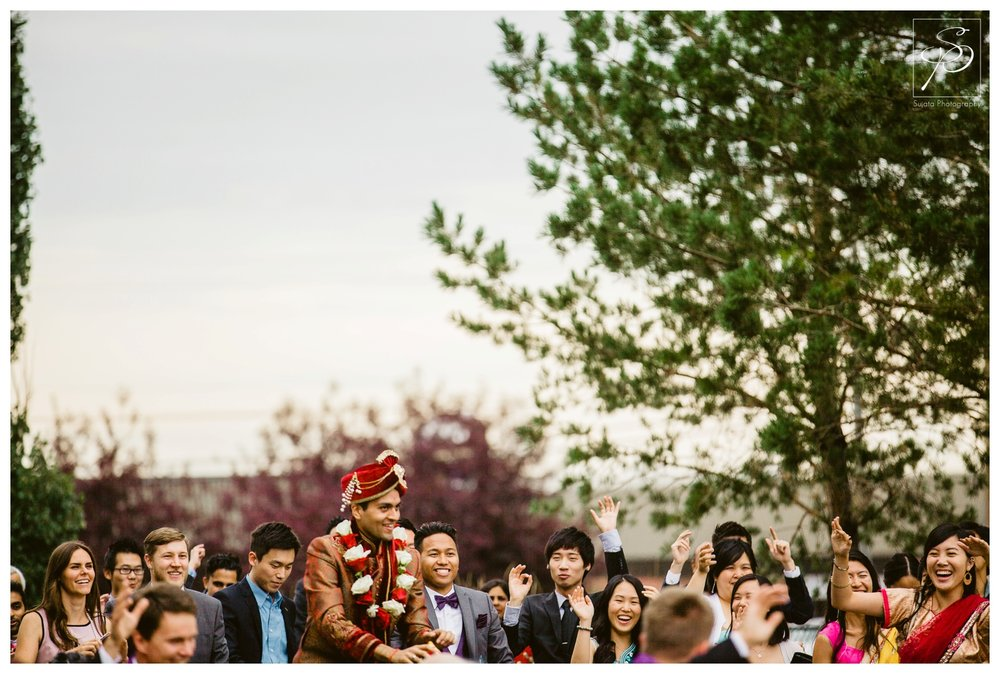 Groom surrounded by guests during east indian barat
