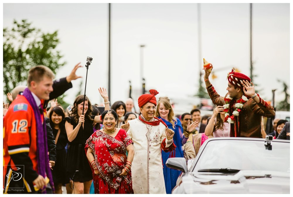 Groom riding in Camaro during Barat at East Indian wedding ceremony Calgary