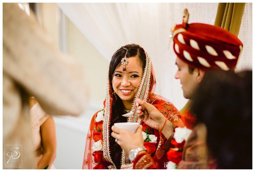 Groom feeding bride honey during their hindu wedding ceremony Executive Royal Inn Calgary