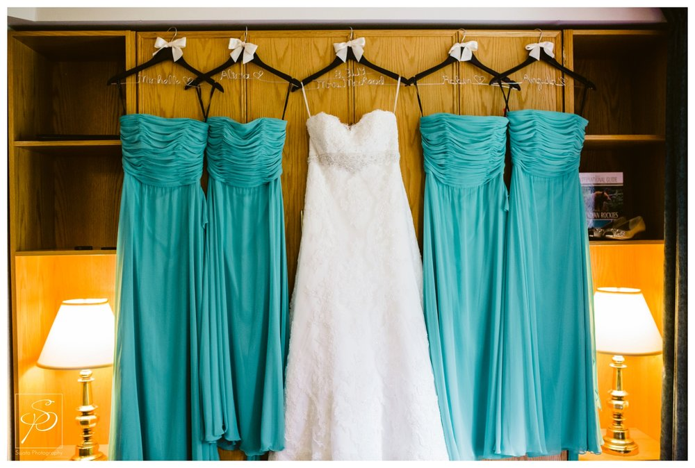 Bridal gown hanging with bridesmaid dresses in Lake Louise