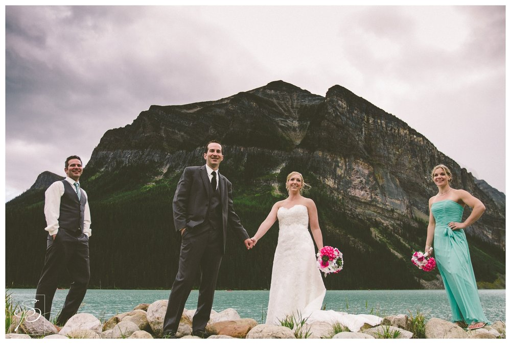 Bridal Party posing at the edge of Lake Louise in Banff