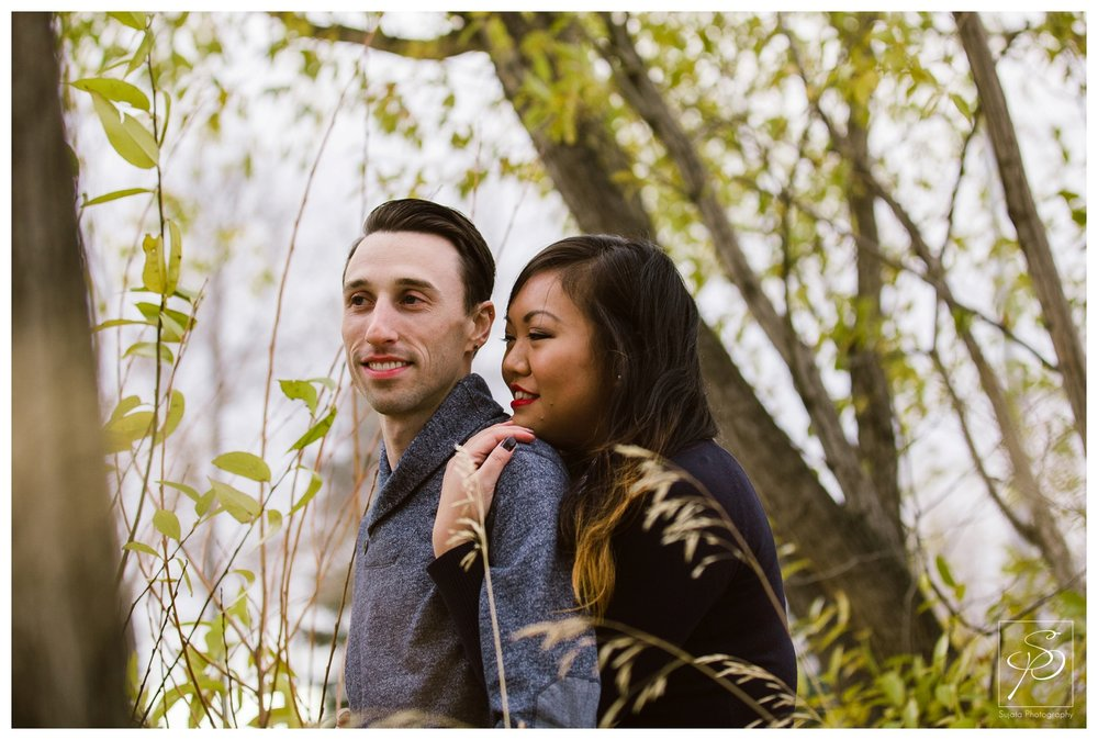 Couple cuddling by the river Calgary Engagement Photography Crystal Sujata