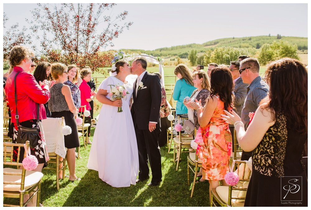 Bride and groom kissing at outdoor wedding ceremony