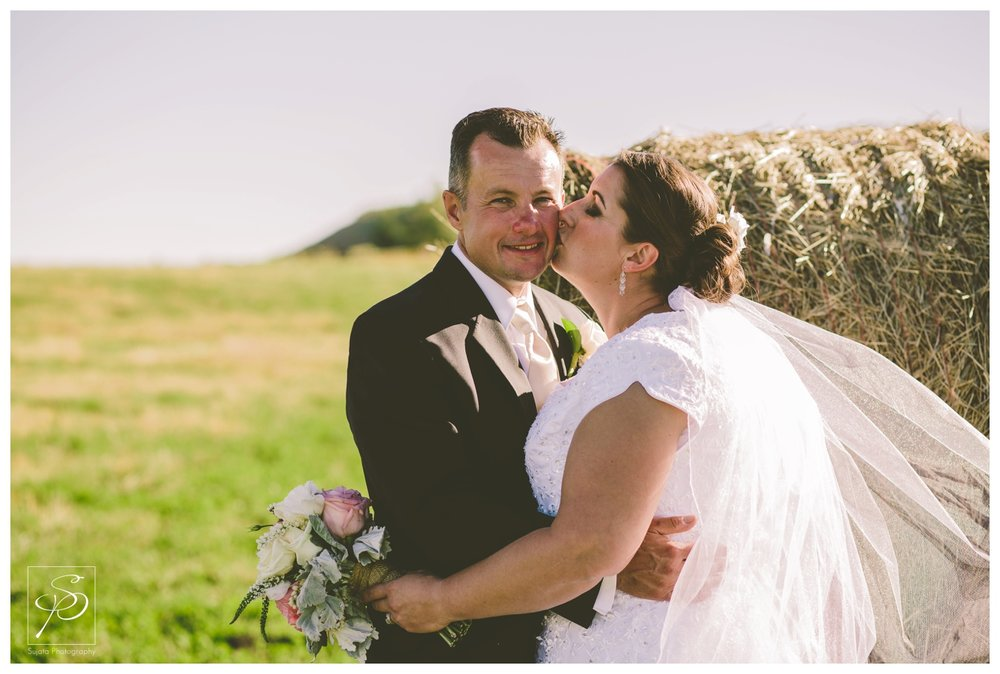 Bride and groom posing with hay bale at acreage wedding