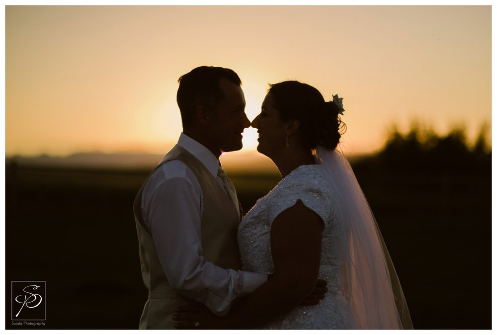 Silhouette of bride and groom at sunset with rocky mountains