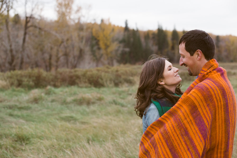Couple cuddling orange blanket