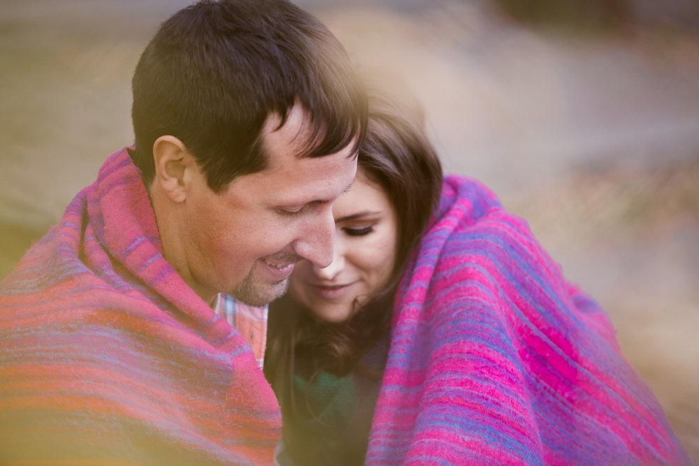 couple cuddling pink blanket