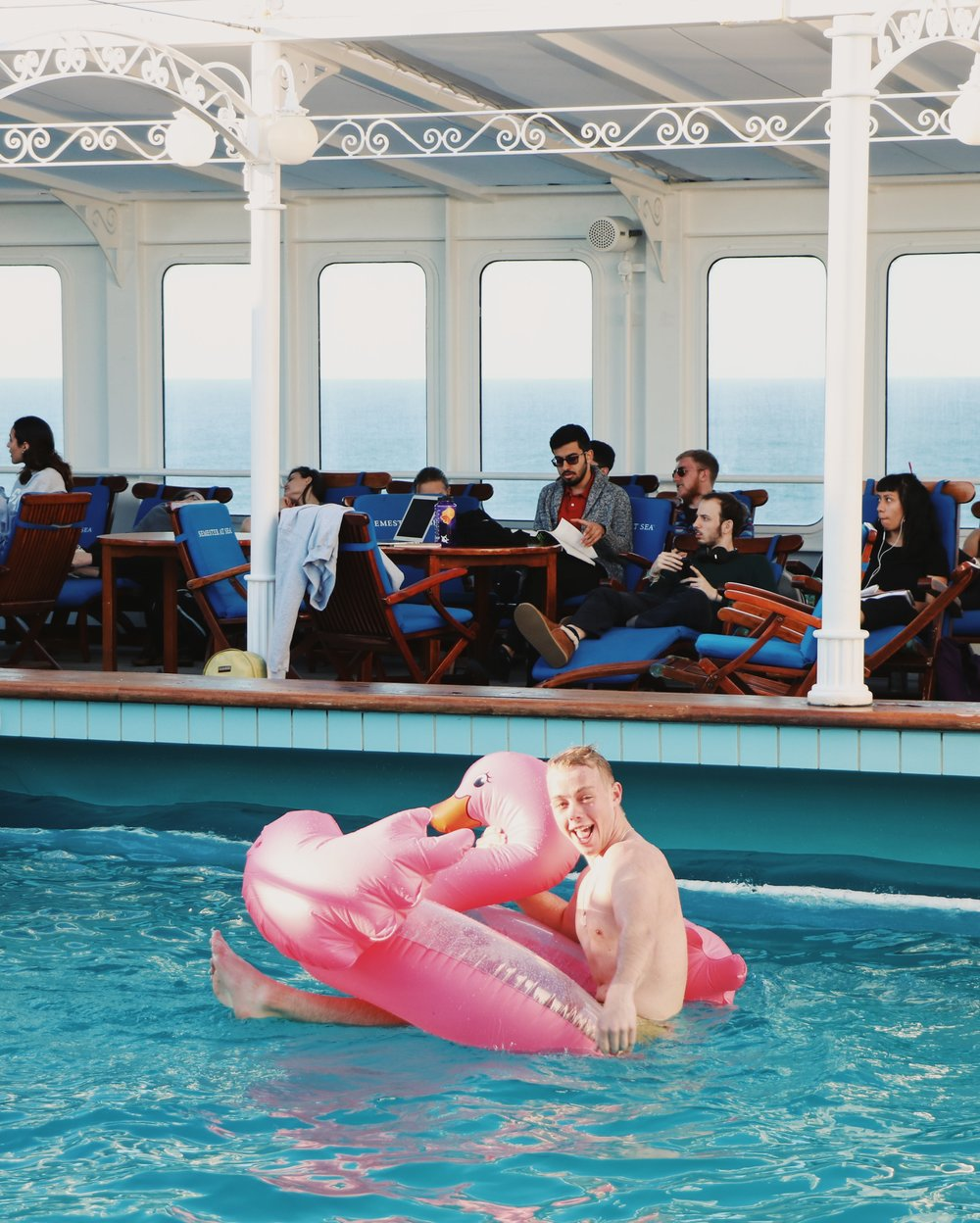 SASer Jack Wold relaxes in a flamingo floaty in the pool. On warm, sunny days, nearly every student can be found tanning on the pool deck in between classes.