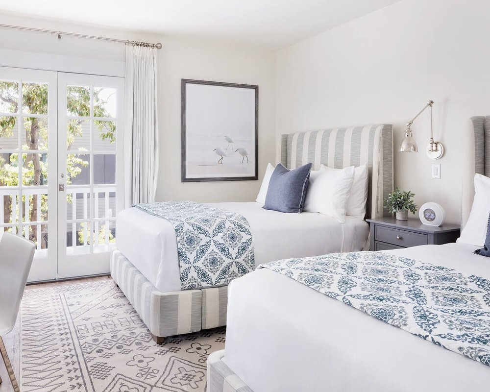 Luxury Two Doubles, Fireplace & Balcony Upstairs - Experience the welcome of coastal southern California in this graciously furnished suite. Featuring two double beds complete with fireplace and French doors opening onto a petite balcony. 285 - 300 sq ftBook Now ➜