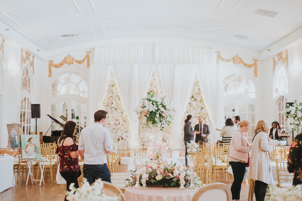 Guests are in a gold and cream 1920s ballroom set up for a wedding with gold Chiavari chairs, blush and cream florals, and live painting