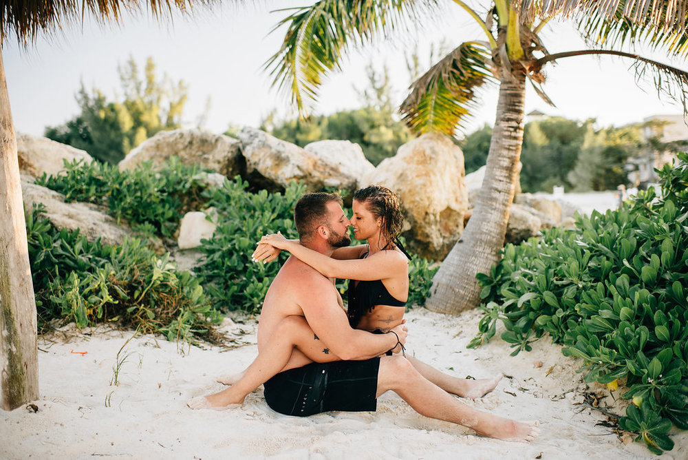 engaged couples snuggling under palm trees in the sand in Jamaica