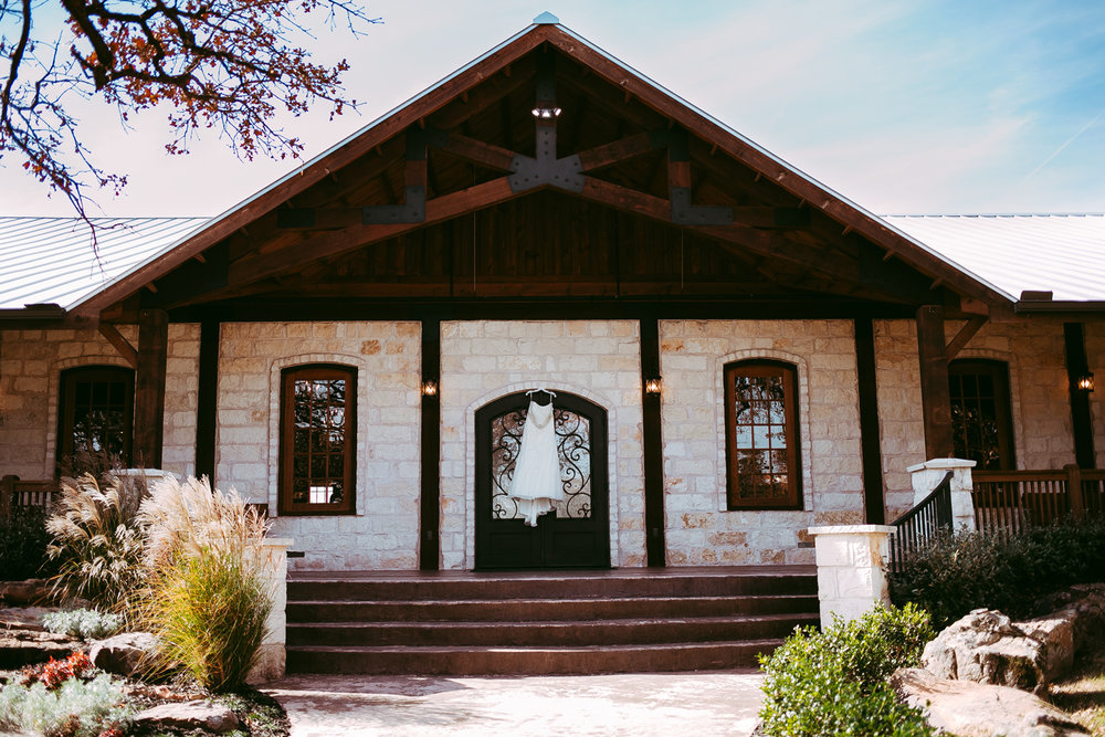 Photo of wedding dress hanging on door at the Springs Event Center in Oklahoma by Amanda Lynn Photography.