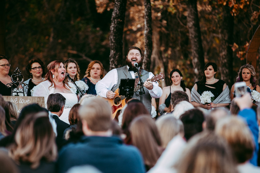 Bride and groom singing during their ceremony at the Springs Event Center in Norman, Oklahoma by Amanda Lynn Weddings.