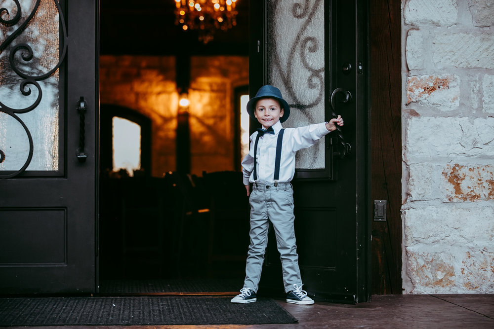 Little boy wearing suspenders and bow tie, holding the door open at the Springs Event Center in Norman, Oklahoma.