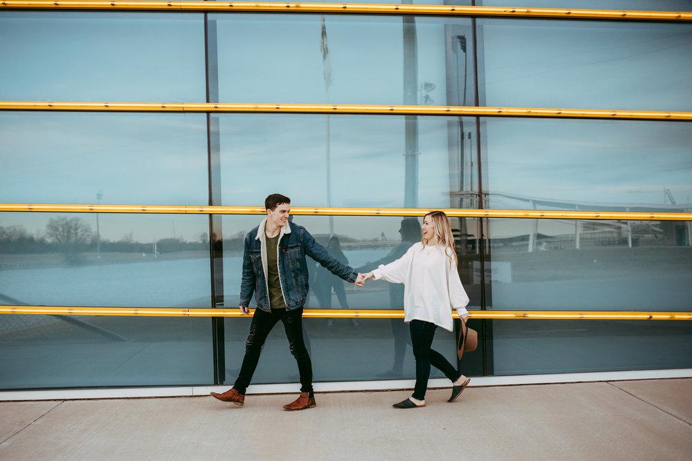 Oklahoma city couple walking and holding hand with the man leading in Oklahoma City by Amanda Lynn.