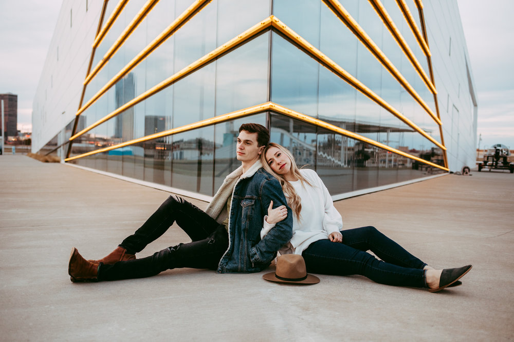 Modern couple sitting on the concrete back to bak at the Oklahoma Boat House District by Amanda Lynn.