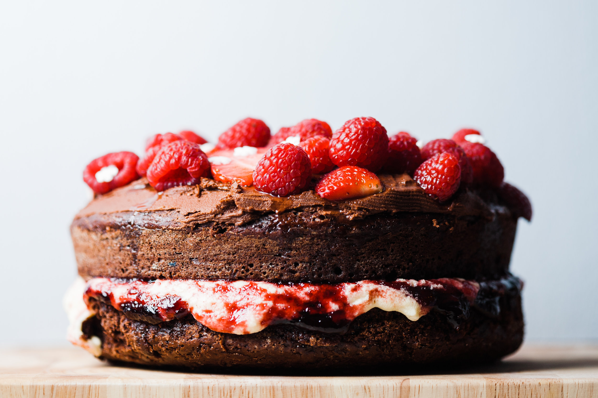 Side view of a vegan chocolate cake with strawberries and raspberries on top